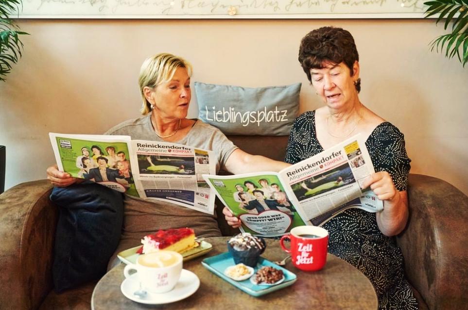 Zwei Frauen lesen im RAZ Café gemütlich Zeitung